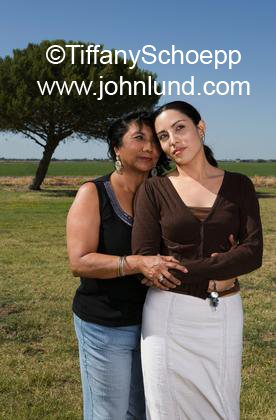 Latina Mother and Adult daughter are hugging outdoors in a green field with ...